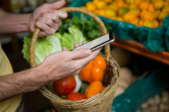 Man using mobile phone while buying vegetables Stock Photography