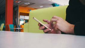 Man using a mobile phone in cafe. Man holds a smartphone in his hands and controls his finger gestures and looks at social networks. Looking through screen stock video footage