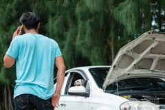 Man using mobile phone and calling for help while the car broken. Stressed asian man using mobile phone and calling for help while the car broken down with his royalty free stock photography
