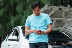 Man using mobile phone and calling for help while the car broken. Stressed asian man using mobile phone and calling for help while the car broken down for royalty free stock photos