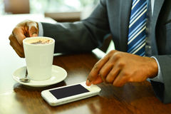 Man using mobile phone in the coffee shop. Close up of man's hands operating mobile phone at restaurant Royalty Free Stock Image
