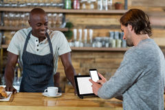 Man using mobile phone at counter. In cafe Stock Photography