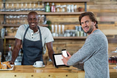 Man using mobile phone at counter. In cafe Stock Images