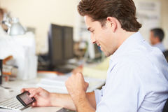 Man Using Mobile Phone At Desk In Busy Creative Office Stock Photo