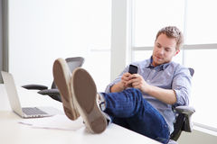 Man Using Mobile Phone At Desk In Design Studio Royalty Free Stock Photo