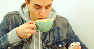 Man using mobile phone while drinking cup of coffee. At cafe stock video footage