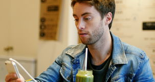 Man using mobile phone while drinking juice stock video footage