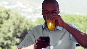 Man using mobile phone while drinking juice. In outdoor restaurant stock video