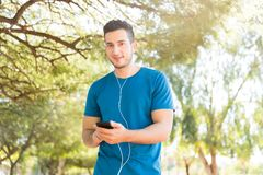 Man Using Mobile Phone And Earphones Before Workout In Park. Young man wearing blue tshirt using mobile phone and earphones before workout in park Stock Image