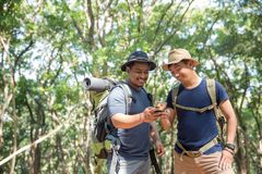 Man using mobile phone in the forest. Two young men using mobile phone in the forest while hiking Royalty Free Stock Photos