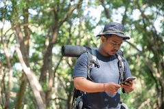 Man using mobile phone in the forest. Young man using mobile phone in the forest while hiking Stock Photo