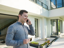 Man using mobile phone in front of his luxury home villa. Young handsome successful man using mobile phone in front of his luxury home villa stock photo