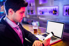 Man using mobile phone with glass of beer and laptop on table at bar counter Stock Image