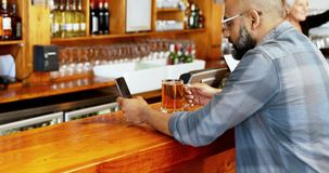 Man using mobile phone while having beer at counter 4k. Man using mobile phone while having beer at counter in bar 4k stock video