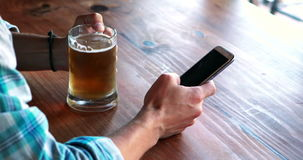 Man using mobile phone while having beer. In pub stock footage