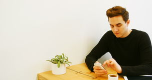 Man using mobile phone while having cup of coffee. At cafe stock footage