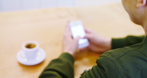 Man using mobile phone while having cup of coffee. At cafe stock video footage