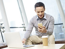Man using mobile phone and laptop Royalty Free Stock Images
