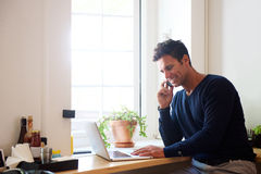 Man using mobile phone with laptop at cafe Stock Photos