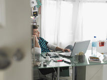 Man Using Mobile Phone And Laptop At Desk Royalty Free Stock Photo