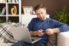Man using mobile phone and laptop. Focus man using mobile phone and laptop at home Stock Photo
