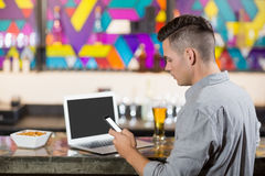 Man using mobile phone with laptop on table at bar counter Stock Images