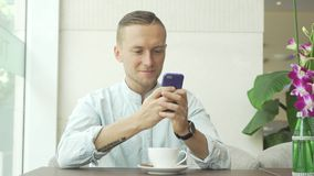 Man using mobile phone laughing and drink coffee stock footage