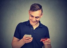 Man using mobile phone making online payment with credit card. Man using mobile phone making online payment with his credit card Stock Photo