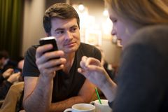 Man using mobile phone during meeting with girl in Stock Image