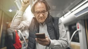 Man using mobile phone in the metro train stock photos