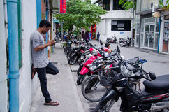 Man using mobile phone near wall on street. Male. Maldives Royalty Free Stock Image