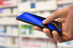 Man using a mobile phone in Pharmacy Royalty Free Stock Photo