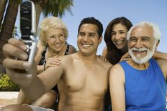 Man using mobile phone photographing self with wife and parents. Royalty Free Stock Photos