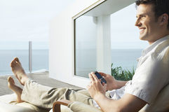 Man Using Mobile Phone On Porch Stock Images