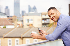 Man Using Mobile Phone On Rooftop Garden Drinking Coffee Royalty Free Stock Images