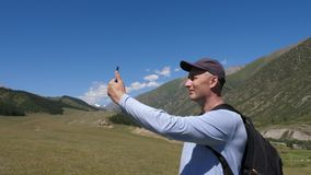 Man using mobile phone for selfie photo in mountain on beautiful landscape stock video