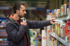 Man Using Mobile Phone While Shopping In Supermarket Stock Images