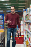 Man Using Mobile Phone While Shopping In Supermarket Royalty Free Stock Image