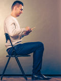 Man using mobile phone sitting in chair. Stock Photos