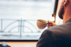 The man using mobile phone, sitting with coffee at cafe stock images