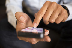Man using a mobile phone on sofa, indoor Royalty Free Stock Photo