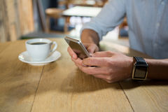 Man using mobile phone at table in coffee shop. Midsection of young man using mobile phone at table in coffee shop Stock Images