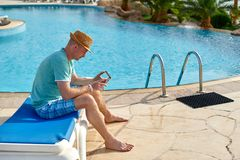 Man using mobile phone on vacation by the pool in hotel, concept of a freelancer working for himself on vacation and. Travel stock photos