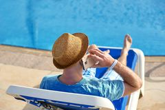 Man using mobile phone on vacation by the pool in hotel, concept of a freelancer working for himself on vacation and. Travel royalty free stock photography