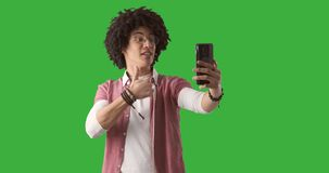 Man using mobile phone for video call on green background. Young man with curly hair using mobile phone for video call over green chroma key background stock video footage