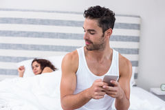 Man using mobile phone while wife sleeping on bed Stock Photography