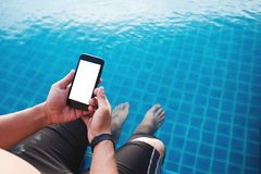 A man using mobile smart phone, blank space on screen, with legs dipping in pool in summer. Clipping path on mobile phone screen Royalty Free Stock Images