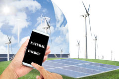 Man using mobile smart phone control with Solar panels,wind turb Stock Photography