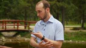 Man using mobile smart phone in park, iphon style. stock footage