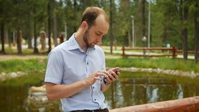 Man using mobile smart phone in park, iphon style. stock video
